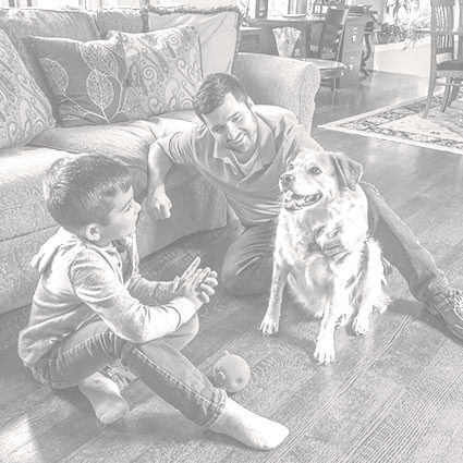 Dad and son sitting on clean hardwood floors with their dog.