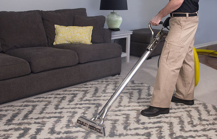 Stanley Steemer technician cleaning an area rug with a wand.