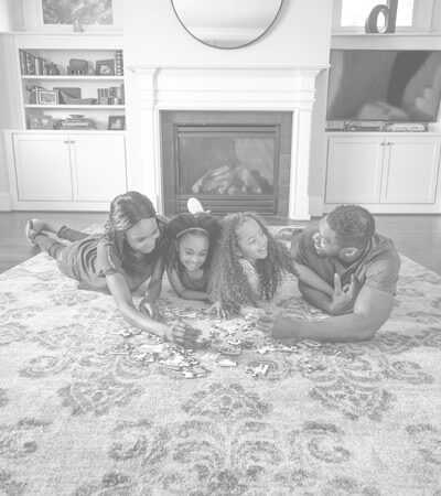Family laying on a clean area rug in the middle of their living room.
