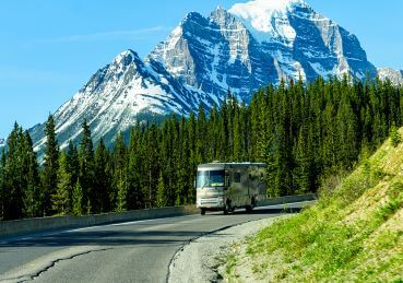 RV driving near mountains and trees