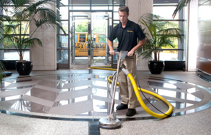Stanley Steemer technician cleaning tile floors in lobby