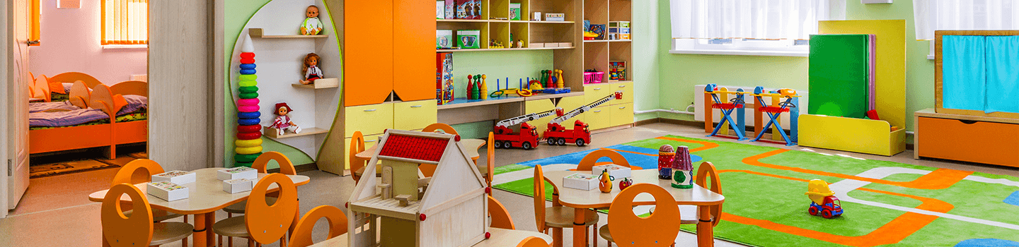 Daycare room with colorful toys, carpet, tables, and beds
