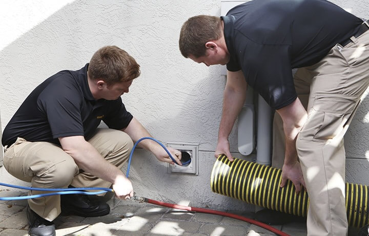 Two technicians cleaning out dryer vents