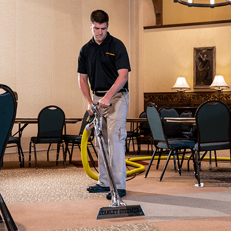 Stanley Steemer technician cleaning carpet in banquet hall