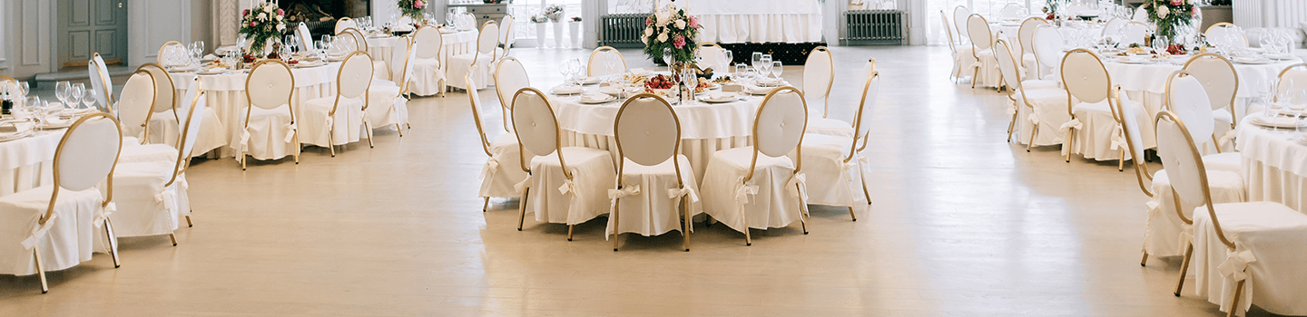Event space with round tables with white covers and chairs