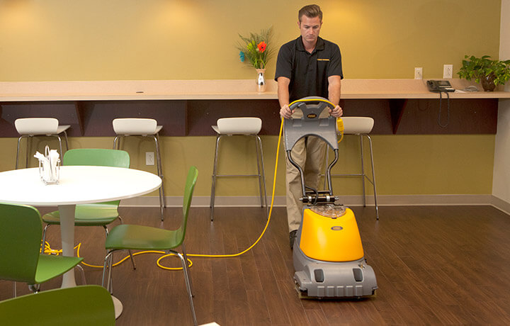 Technician performing commercial cleaning services to hardwood