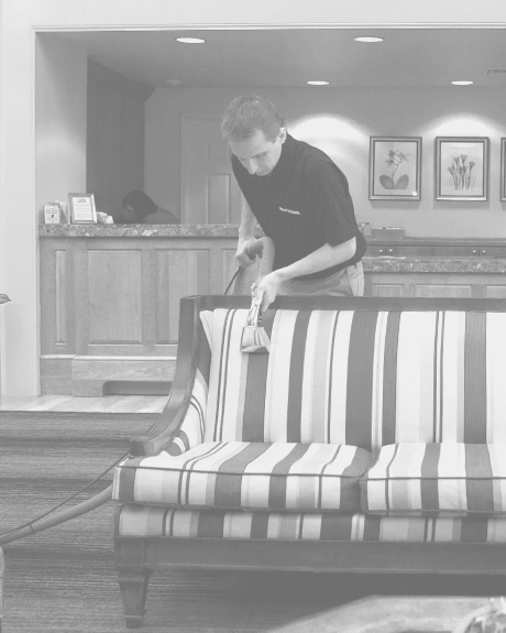 Stanley Steemer technician cleaning fabric upholstery in hotel lobby