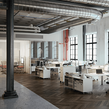 Desks inside industrial building with vents showing