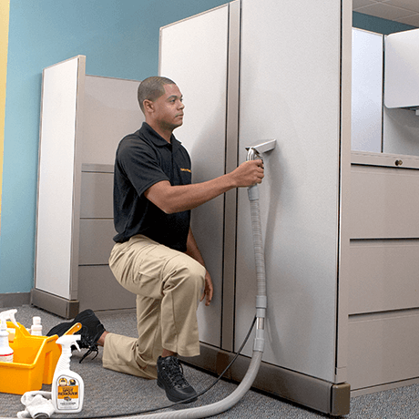 Stanley Steemer technician cleaning cubicle fabric