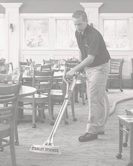 Stanley Steemer technician cleaning carpet in dining area of restaurant