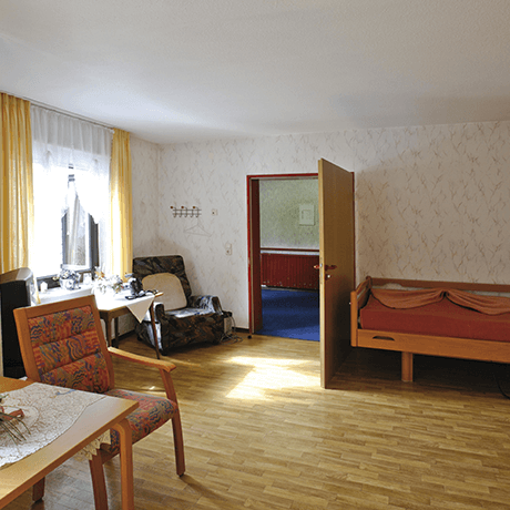 Nursing home bedroom with laminate floors and upholstered furniture