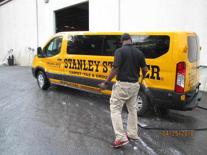 Atlanta, Georgia crew member cleaning the exterior of a carpet cleaning service van.