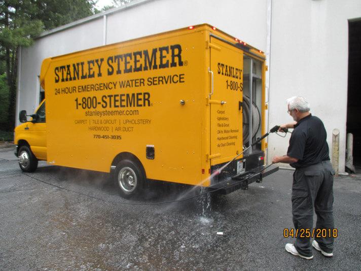 Atlanta, Georgia crew member cleaning the exterior of a carpet cleaning service van.