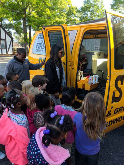 Augusta, Georgia crew members showing kids the inside of a Stanley Steemer service van at career day.