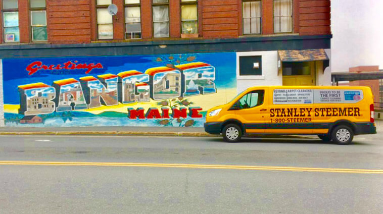Stanley Steemer service van parked in front of a graffiti wall that says Greetings from Bangor, Maine