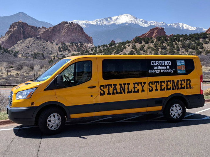 Carpet cleaning service van parked outside with Pikes Peak scenery in the background in Colorado Springs, Colorado.