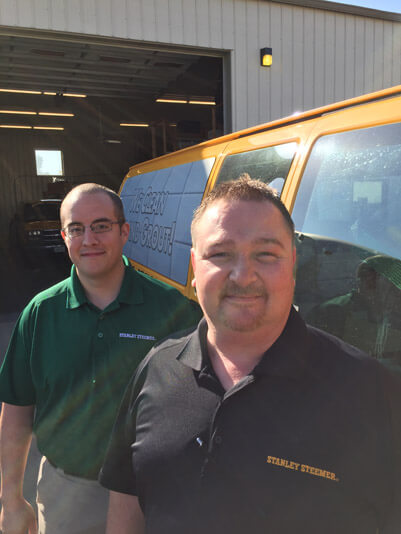 Crew members Doug and Jon standing in front of their Stanley Steemer service van in Columbia, Missouri.