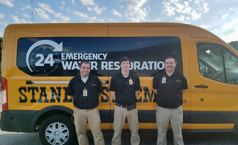IICRC Certified Water Mitigation Team in Cordova, Tennessee standing in front of a water damage restoration service van.