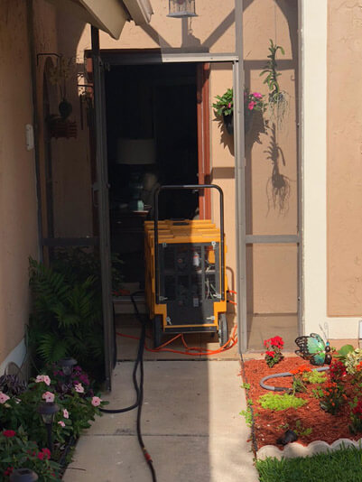 Air duct cleaning equipment sitting in the doorway of a customer's home in Delray Beach, Florida.