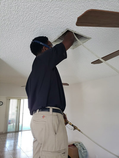 Delray Beach, Florida air duct cleaning technician cleaning an air vent in a customer's ceiling.
