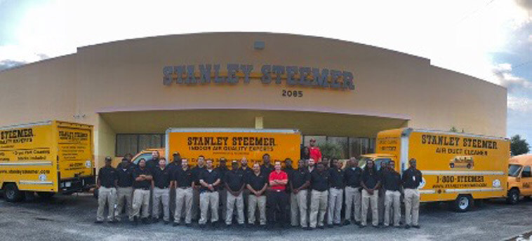 Delray Beach, Florida crew standing in front of service vans in their office parking lot.