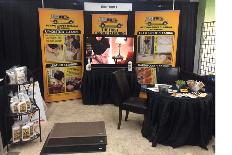Booth displaying cleaning service information and cleaning products at a home show in Des Moines, Iowa.