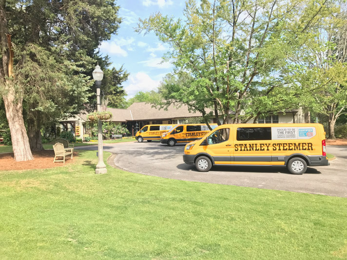 Stanley Steemer carpet cleaning vans in front of a house in Hoover Alabama