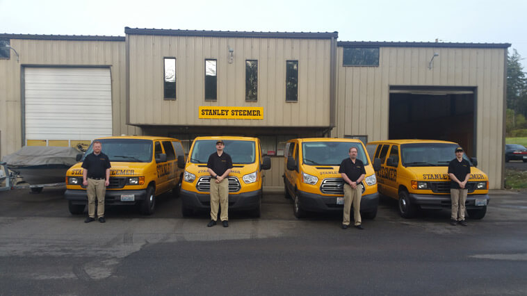 Stanley Steemer Technicians posing in front of carpet cleaning vans