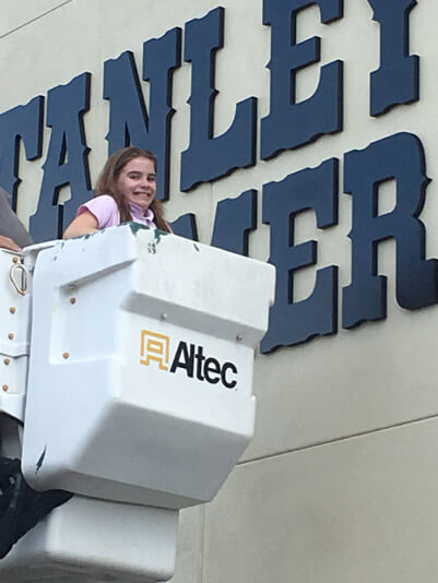 Girl in Cherry picker in front of Stanley Steemer building in Lakeland Florida
