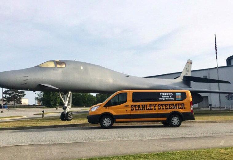 Stanley Steemer carpet cleaning van in front of plane in macon georgia