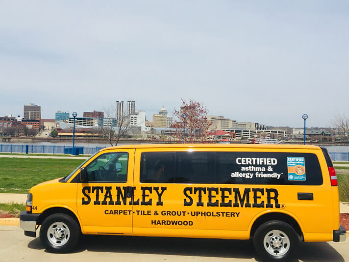 Stanley Steemer carpet, tile & grout upholstery van in front of Peoria, Illinois skyline.