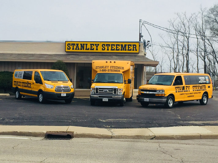 Fleet of carpet cleaning, hardwood, and air duct vans parked in front of the Peoria, Illinois office.