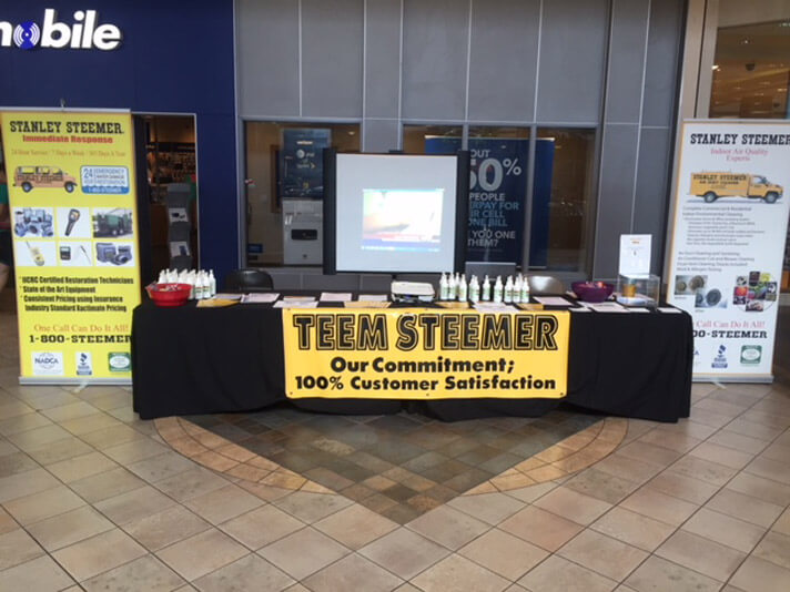 Teem Steemer of Port Saint Lucie, Florida display their cleaning services with a table at Hurricane Expo.