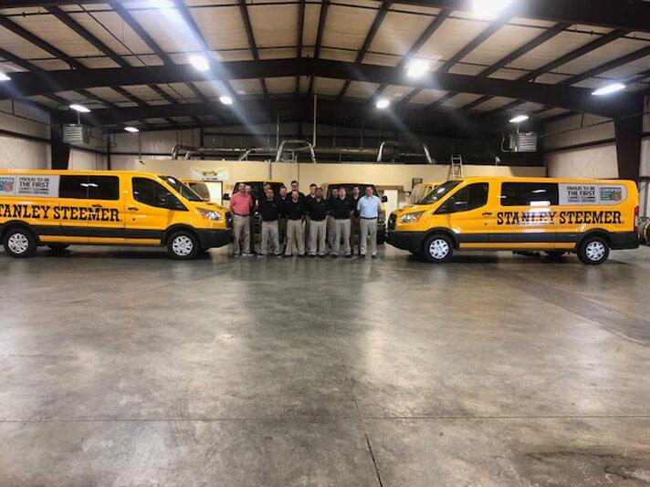 Carpet cleaning vans and Stanley Steemer team inside Springdale, Arizona branch warehouse.
