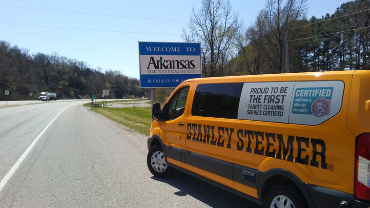 Certified carpet cleaning service van parked in front of welcome to Springdale, Arkansas sign.