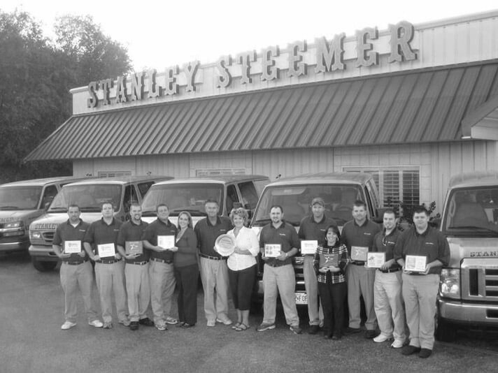 Spingfield, Missouri crew standing in front of Stanley Steemer service vans in their office parking lot.