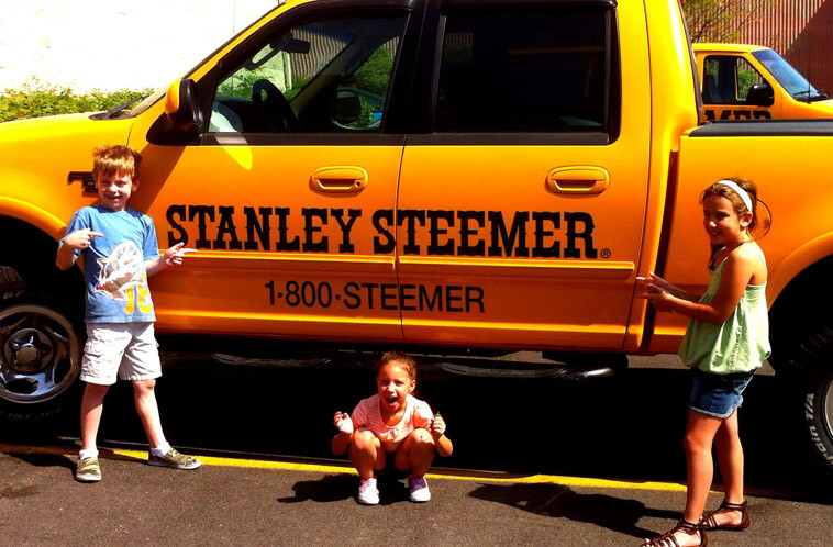 Excited kids standing in front of Stanley Steemer service vehicles in Youngstown, Ohio.