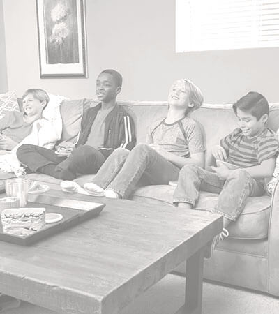 Young kids sitting on a couch in a living room.