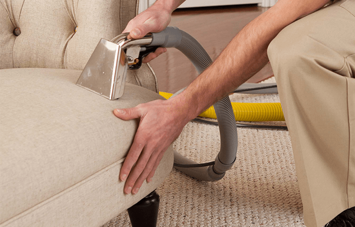 Technician using hot water extraction machine to clean upholstery