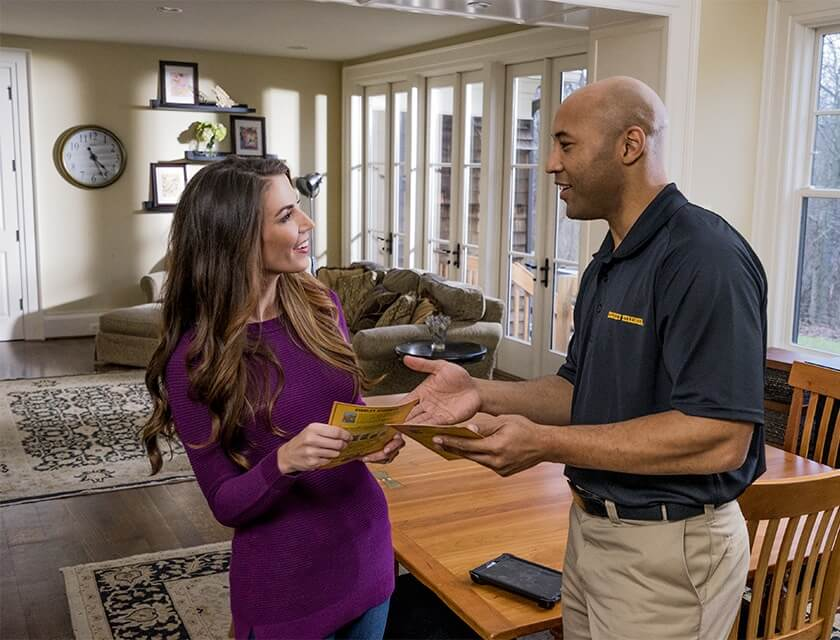 Stanley Steemer technician talking to a happy customer in their home.