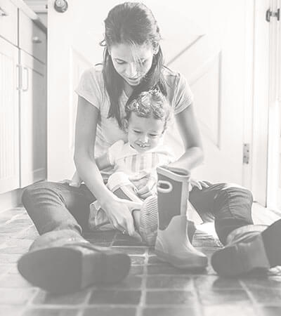 Mother and daughter sitting on a natural stone floor in their kitchen.