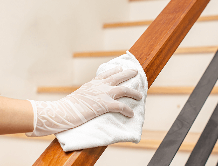 Close up of person wearing gloves disinfecting handrail