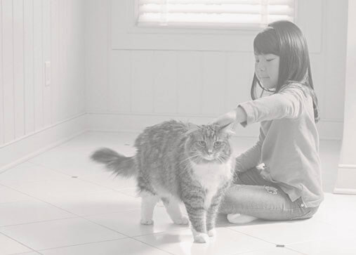 Girl sitting on a tile floor with her cat.