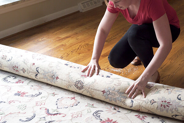 Woman moving rug to clean hardwood