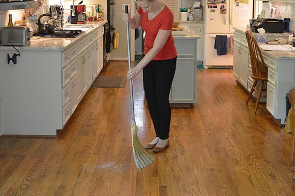 Homeowner sweeping hardwood floors