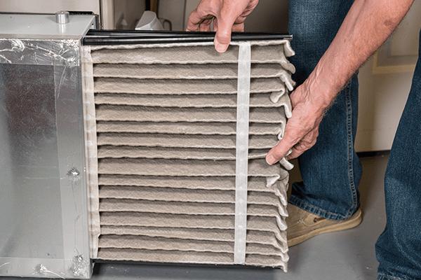 Man replacing air filter in his HVAC system