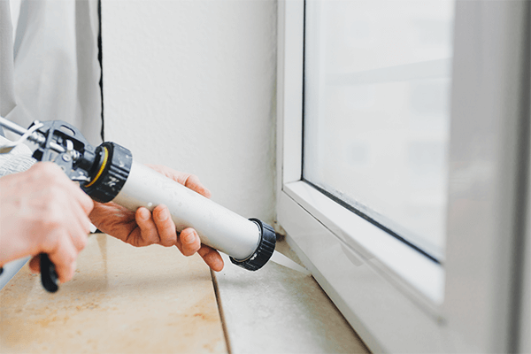 Person caulking the windows to seal drafts