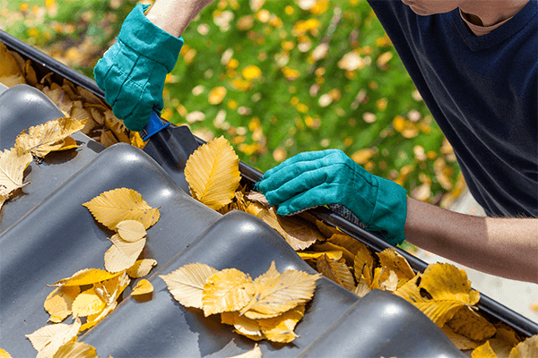 Man cleaning gutters and removing leaves with shovel