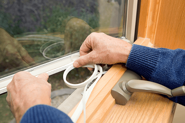 Person weatherstripping  windows in home