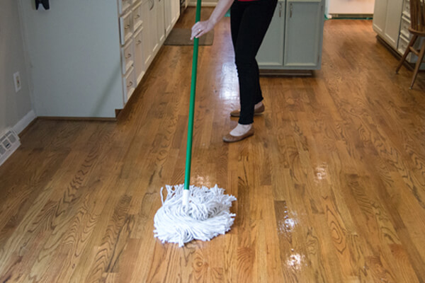 Woman mopping and cleaning hardwood floor in kitchen